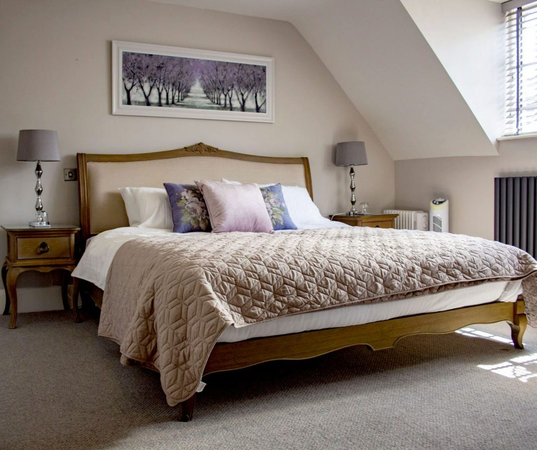 A room with a lot of light and king-size bed.